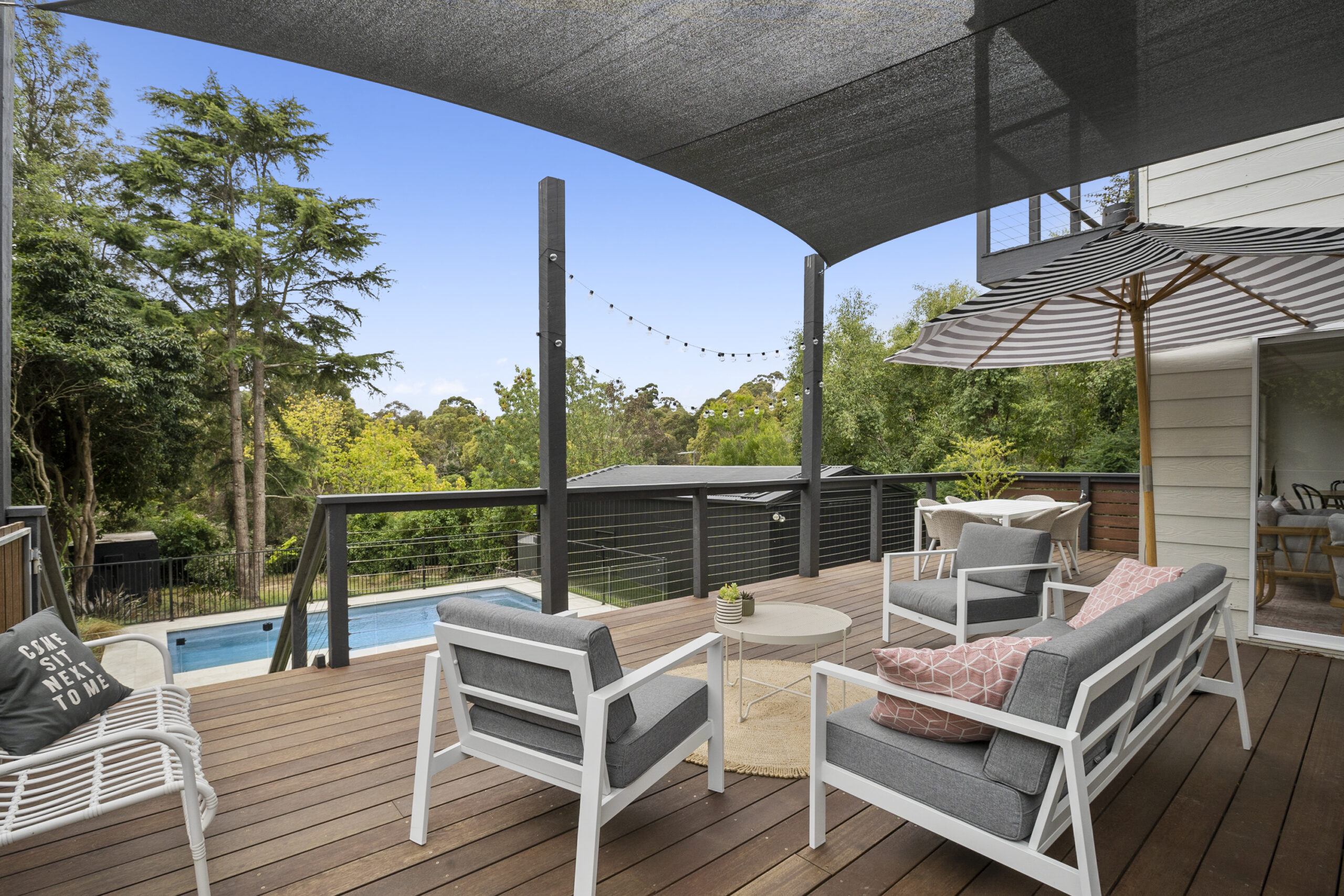 Afresco lounge and dining zone on deck overlooking pool. The Grove. Mt Martha Holiday rental